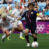 Good start: Japan's Aya Miyama vies for the ball with Canada's Kaylyn Kyle during their London Olympics Group F match on Wednesday in Coventry, England. Japan won 2-1. | AP
