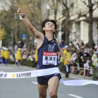 Toyo University anchor Takashi Saito crosses the finish line at the annual Tokyo-Hakone collegiate ekiden road relay on Tuesday. | KYODO PHOTO