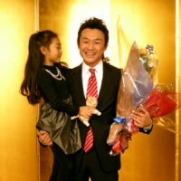 Tender moment: Toshiaki Nishioka holds his daughter, Kohime, at a Tokyo news conference on Tuesday.