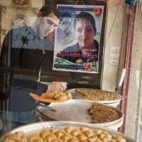 Still near: Sami Badawi puts out baklava pastries under the gaze of his deceased friend, Abdullah Muzannar, who is featured on a poster at the Jabalya refugee camp sweet shop where they worked together. | THE WASHINGTON POST