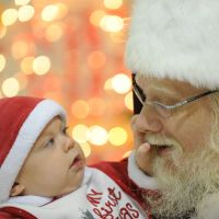 Seeing is believing: A baby takes a close look at John Parks, playing the role of Santa Claus, as he greets children at an elementary school in Ashburn, Virginia. | THE WASHINGTON POST