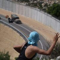 Slings and stones: A Palestinian tries to sling a rock at Israeli soldiers as they patrol the controversial separation barrier built by the Jewish state during clashes near the village of Bilin, west of Ramallah, in April.   AFP-JIJI