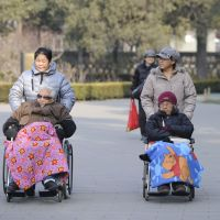 Keeping mobile: Two elderly people are pushed on wheelchairs at a Beijing park Tuesday. | AFP-JIJI