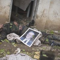 Base overrun: The body of a Syrian Army soldier lies on the ground Sunday at an infantry base that rebels claim to have captured in the village of Tal Sheer, Aleppo Province. Placed atop him is a picture of the late President Hafez Assad. | AP