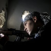 Reinforcements: A Free Syrian Army fighter aims his weapon during clashes with government forces in Aleppo on Dec. 10. | AP