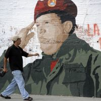 Larger than life: A man walks past a painting of cancer-hit Venezuelan President Hugo Chavez in Caracas on Friday. | AFP-JIJI