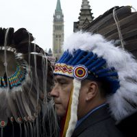 On the warpath: Aboriginal chiefs taking part in a protest stand at the main gate to Parliament Hill in Ottawa on Friday. | AP