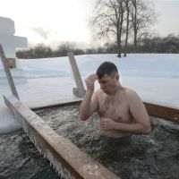 Baptism of ice: A man crosses himself as he bathes in a frozen pond in Moscow's Kolomenskoye Park on Saturday. | AP