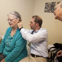 Quality metrics: Physician assistant Keith Bell, of Mosaic Medical in Bend, Oregon, examines Marilyn Gribble, accompanied by her daughter, Deborah Gribble. Oregon's health care plan has focused on making high-quality care less expensive. Integrating systems, such as physical, dental and mental health, is part of the approach. | WASHINGTON POST