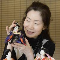 Takako Yoshino holds a 'fukuyose bina' (good luck-inviting hina doll)  | KYODO PHOTO