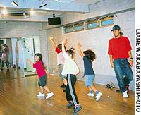 Teacher Satoshi Yamamoto with elementary school girls in his hip-hop class at U-Pride