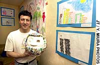 Hector Sierra holding up the daruma made by Japanese and American children