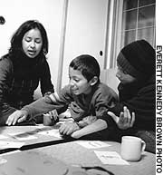 Nhora Prieto and her two sons, Victor and Brandon, improve their Japanese skills with a game of Hiragana cards.