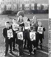 Gina Edens (right) stands with a fellow Japanese-language teacher and their pupils in front of the Whitgift School, south of London.