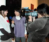 Fourth year student Sachi Shigeno is interviewed by local media after selling her painting 'Fireworks,' one of the highest bid artworks at the auction.