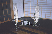 Carved-wood flowers adorn the household altar (top) while Hiroyasu Isoda demonstrates how to make them.