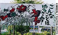 A protest sign near the site uses the image of a tengu, one of the long-nosed avatars said to inhabit Mount Takao. The slogan says: 'This can't be  forgiven.'