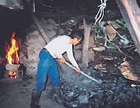 A pile of charcoal is raked while a new fire starts to blaze in the kiln.