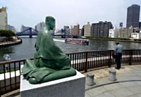A statue of Basho with Kiyosumi Bridge in the background.