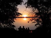 A family of fellow canoeists watches the sun set by their campfire beside Kabelick Lake in the Muritz National Park 100 km from Berlin.