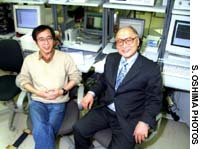 Bio-Emissions Laboratory head Mikio Yamamoto (right) sits with a researcher.