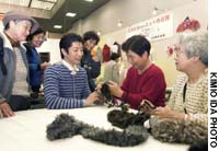Mitsuharu Hirose (center) explains the finer points of knitting to visitors at a Kyoto craft fair.