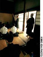 Monks wielding 'encouragement sticks' stand over visitors to a Kyoto monastery.