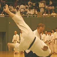 Roland Thompson, shown throwing an aikido opponent, says, 'If more people studied martial arts, it would be good for the world,' as more people would learn to manage dangerous situations without causing harm.