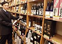 Owner and manager Yoshitaka Inomata displays one of the 3,200 varieties of   shochu  on the shelves of his Sho-chu Authority store in Shiodome, Tokyo.