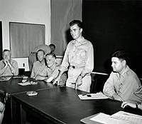 Col. Paul W. Tibbets (standing), the pilot of the B-29 that dropped the atomic bomb on Hiroshima, describes the flight during a news conference at Strategic Air Force headquarters on Guam, Aug. 7, 1945. Maj. Gen. Curtis E. LeMay sits on the far right.