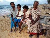 Perumal and his wife, Sinnapillai, sit with their grandchildren Rokshan and Rojine in the northern Sri Lankan province of Jaffna, near the spot where they were hit by a giant wave during the December tsunami.