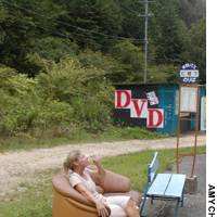 Enjoying a bus stop in the countryside with all the conveniences of home: beer, a sofa and pornographic DVDs.