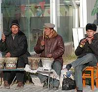 Uighur buskers play on a glitzy shopping street in the Han part of Korla