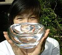 Joy Suzuki shows one of her specialty flower vases. She now also is keen to design sandblasted and etched windows for homes and businesses.