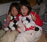 Nami-chan (above right) put her elders to shame by photographing the rare and elusive smiley face firework. Here she enjoys the display with her sister Miho-chan, considerately toting toy cows from we wonder who.