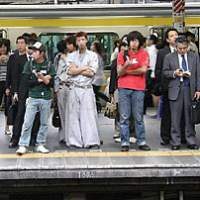 Passengers wait in orderly fashion for the train