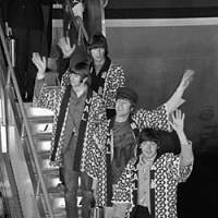 The Fab Four arrive at Haneda Airport in Tokyo on June 29, 1966 (top) wearing JAL-issued happi jackets. The day after, amid tight security (bottom top), they played their first concert at Nippon Budokan Hall. Those with good eyes may spot the souvenir near John Lennon's feet on the album cover that he reportedly bought when he dodged his minders and went shopping in Tokyo. | KYODO PHOTOS
