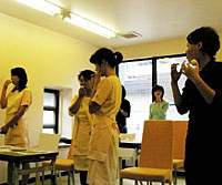 Omori Group dental clinic workers undergo training in breathing control with the help of Ping-Pong balls in the mouth. | REIJI YOSHIDA PHOTOS