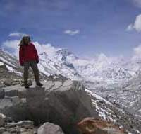 Takao Arayama stands atop a boulder with Mount Everest behind.