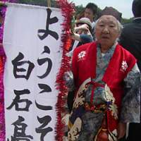 Man-chan, along with his friend Kio-chan, are there in a flash when visitors to Shiraishi arrive. The banner reads, 'Welcome to Shiraishi Island.'   AMY CHAVEZ PHOTO