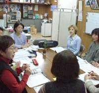 Local housewiveswho are supporters of Kyoto Prefectural Assemblyman Hiroshi Mizuguchi gather at his office (top) for one of the twice-monthly English lessons given by his wife, Jane Singer Mizuguchi (second from right). Part of Singer's constituency work involves visiting supporters to ask permission to put up posters on their property (above), and then putting up the posters, which must conform to strict laws governing their size and style (below).   ERIC JOHNSTON PHOTOS