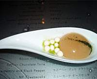 Jeff Ramsey (top) makes carrot caviar in the Molecular Tapas Bar, which uses the same sodium alginate as the miso soup (middle); while a customer (above) squeezes his own soba through a syringe, prior to tucking into the odd-looking apricot-and-coconut dessert (below) — then perhaps heading off to the picturesque mensroom (bottom). | YUMI WIJERS-HASEGAWA PHOTOS; PHOTO COURTESY OF MADARIN ORIENTAL