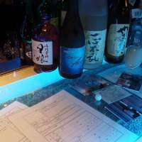Bottles on the bar's counter, and detectives' surveillance reports under it