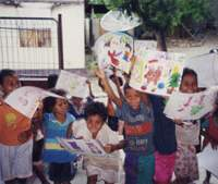 East Timorese children in Dili hold drawings from their penpals in Japan in 2000, four months after their world had been terrorized. | PHOTO COURTESY OF ARTISTS WITHOUT BORDERS