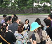 Ms. Hirose, A Hato Bus tour guide, addresses her guests as their bus approaches Rainbow Bridge in Minato Ward.