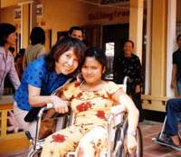 Michiyo Yoshida, cofounder of Go! Fly! Wheelchairs (top), in Vietnam with a woman who received a used wheelchair from the nonprofit group in 2005; Masae Tsujioka (above), delivers a wheelchair to a sick child and his mother in Burkina Faso in May this year; and three Nepali recipients of used wheelchairs from Japan with their families and friends and Bijay Giri (front right, below), who delivered them in November 2006. | PHOTOS COURTESY OF GO! FLY! WHEELCHAIRS, MASAE TSUJIOKA and BIJAY GIRI