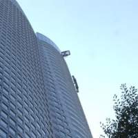 A window-cleaning gondola descends the side of the Mori Tower in Roppongi Hills from 250 meters up.