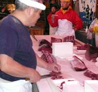 Men cuts up slabs of tuna at the annual Oma Tuna Festival in Aomori Prefecture. | HILLEL WRIGHT PHOTO