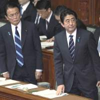 Eyes right, again: Prime Minister Shinzo Abe (right) and his deputy and finance minister,  Taro Aso, of the Liberal Democratic Party are back in control of Japan after both being forced out of the prime ministerial job within a year in 2007 and 2009, respectively. | BLOOMBERG