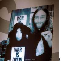 A display shows John Lennon and Yoko Ono in 1969, with bags of acorns to be sent to world leaders as a symbol of peace.